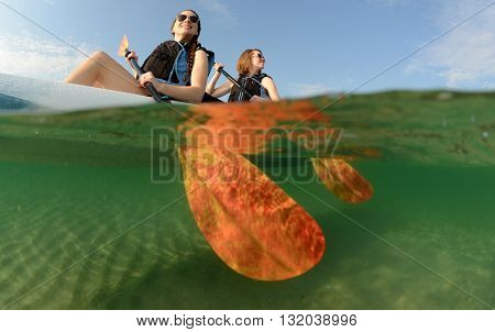 Two young women smiling in kayak off of the coast of Florida