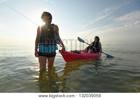 Two young fit women smiling in pink kayak