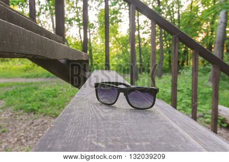 Retro sunglasses on wooden stairs in summer park