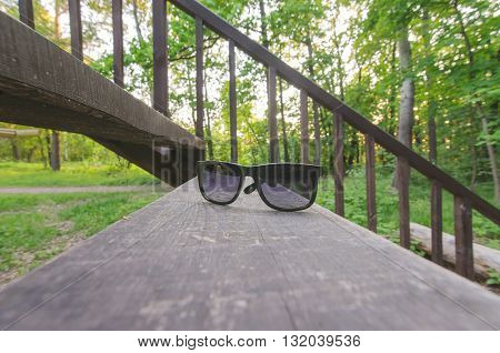Fashion sunglasses on wooden stairs in summer park