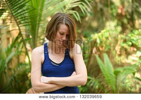 A young woman crying with arms crossed across chest because of stress