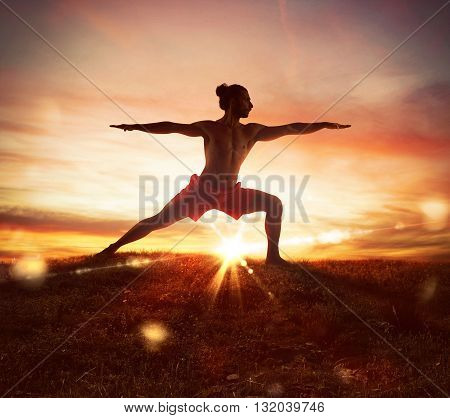 Man in a yoga position at sunset