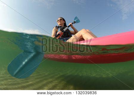 Youg woman wearing life vest in pink kayak