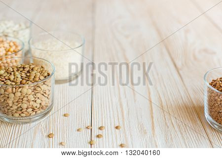 Grain and beans in glass bowls on a white wooden background. Various types of grain. beans, peas, buckwheat, lentils, rice. background of white boards. healthy food and diet concept.