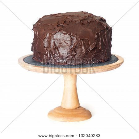 Chocolate cake on wooden stand isolated on white background