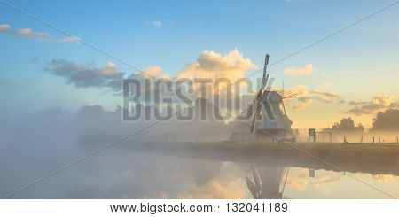 Panorama Of White Wooden Windmill In Morning Fog