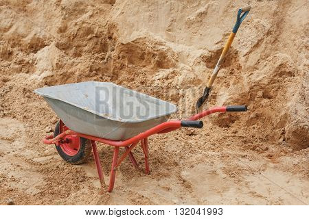 Construction wheelbarrow filled with sand work with a shovel