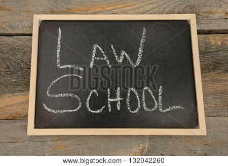 Law School written in chalk on a chalkboard on a rustic background