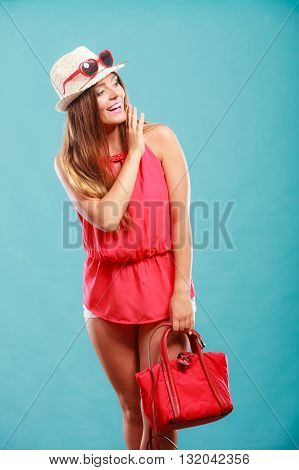 Cute attractive young woman girl in red shirt and straw hat with handbag and sunglasses in studio on blue. Summer female fashion vogue.