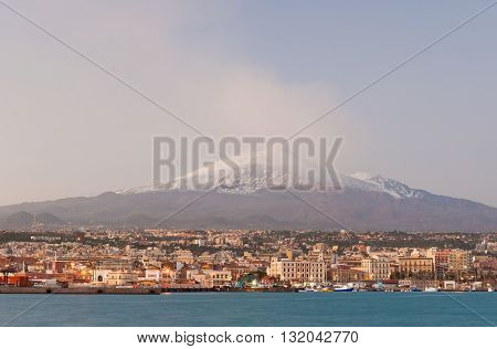 Skyline of Catania with snowy volcano Etna in background during the winter after the sunset
