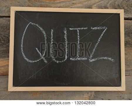 quiz written in chalk on a chalkboard on a rustic background