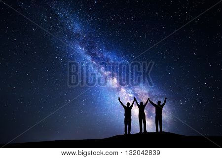 Landscape with colorful Milky Way and silhouette of a happy family with raised-up arms on the mountain. Night starry sky. Beautiful Universe. Space background