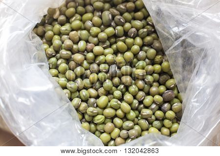 Plastic bag with Green mung beans. Selective focus. High angle view
