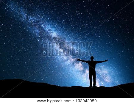 Night colorful landscape with Milky Way blue city lights and silhouette of a standing sporty man with raised up arms on the mountain. Beautiful Universe. Travel background with blue sky full of stars. Lifestyle background