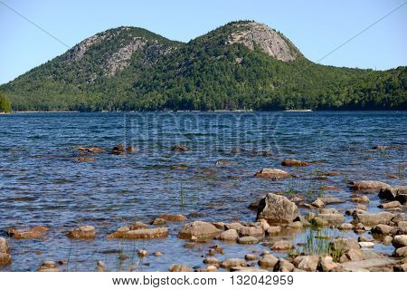 Summertime in Acadia National Park in Maine with view of river rocks and mountain