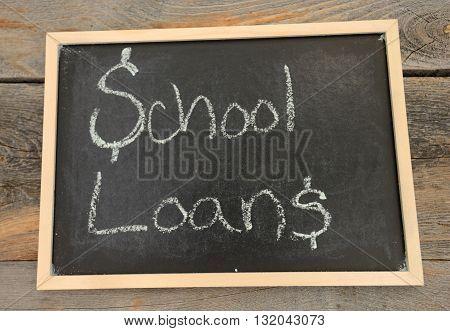 school loans written in chalk on a chalkboard on a rustic background