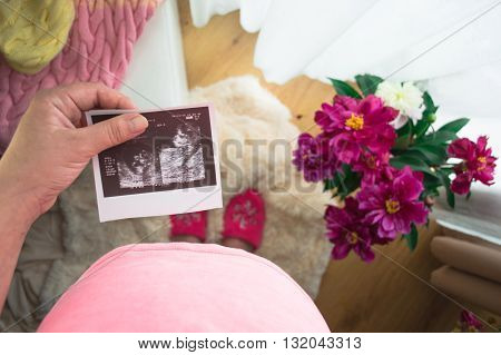 Pregnant Woman Looking At X-ray In Bedroom with Peonies