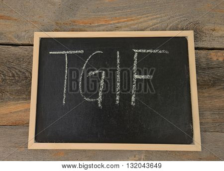 TGIF written in chalk on a chalkboard on a rustic background