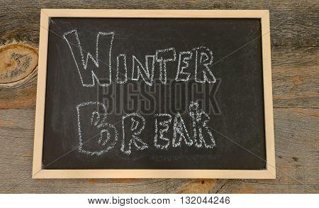 winter break written in chalk on a chalkboard on a rustic background