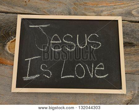 jesus is love written in chalk on a chalkboard on a rustic background