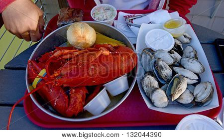 Lobster and oyster seafood dinner on a tray at a restaurant