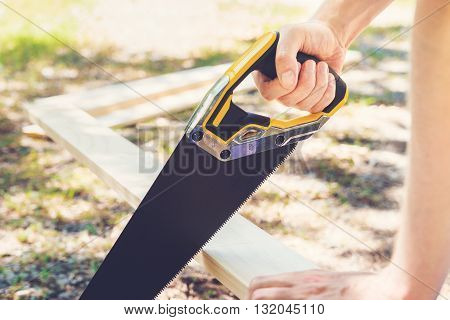 Man Sawing A Wood Board Outdoors