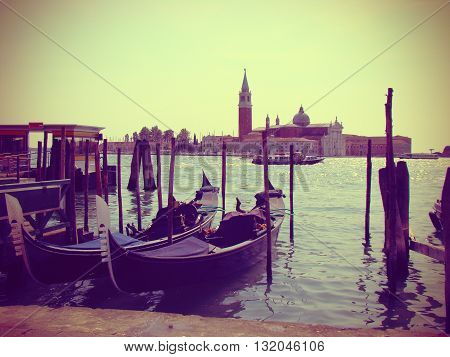 Moored gondolas in Venice vintage toned. Gondolas moored by Saint Mark square. View of the San Giorgio di Maggiore from Piazza San Marco. Venice Venezia Italy Europe.