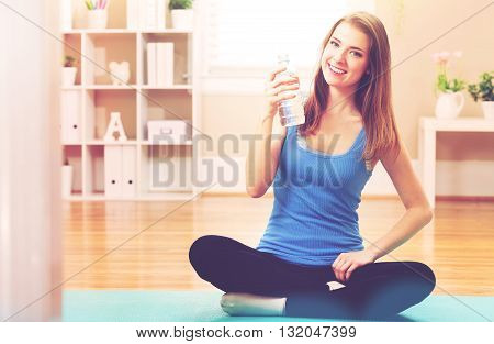 Happy Athletic Woman With A Bottle Of Water In Her Studio