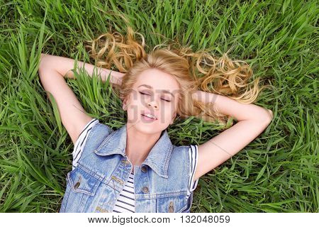 Young beautiful woman on green grass