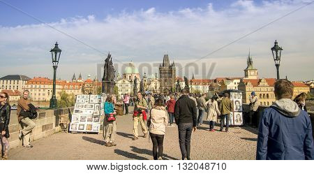 Prague Czech republic - April 22 2015 - Busy Charles Bridge in the capital of Czech republic Prague. Charles Bridge is a historical and most famous bridge in Prague. It is very popular both with tourists and locals.
