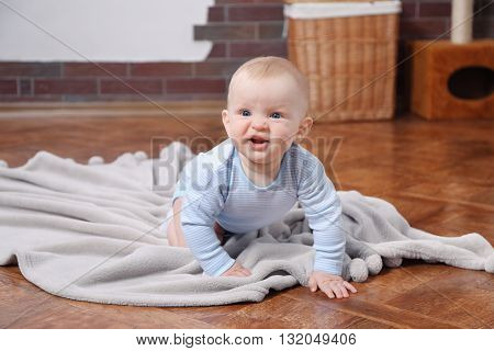 Crawling baby on the blanket in the room