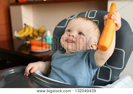 Baby holding carrot in a chair