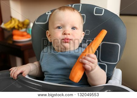 Baby eating carrot in a chair