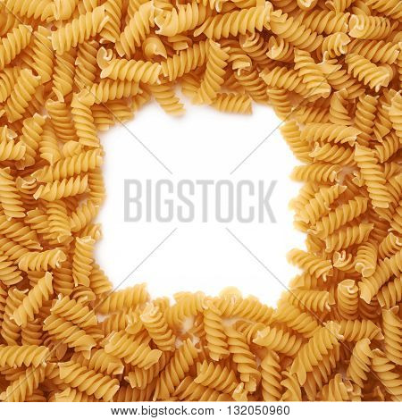 Square frame made of dry rotini yellow pasta over isolated white background