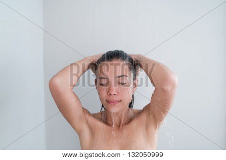 Woman relaxing showering in luxury hotel spa shower or home bathroom. Asian young adult enjoying body relaxation in hot warm water washing hair cleansing from conditioner product.