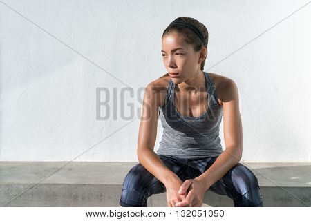Asian fitness runner woman thinking pensive during workout. Serious athlete model on gym break tired feeling unsatisfied, depressed about weight loss progress or self-esteem confidence. Active living.
