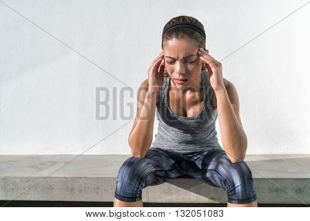 Athlete fitness running woman with headache migraine pain during cardio workout run. Asian athlete with health problem feeling exhausted during difficult strength training exercise at gym.
