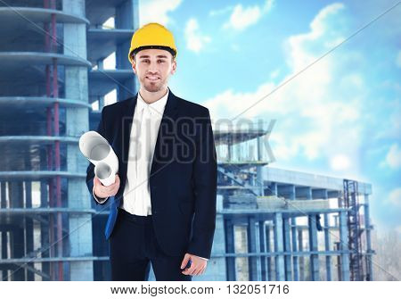 Professional engineer with blueprint on blurred construction site background