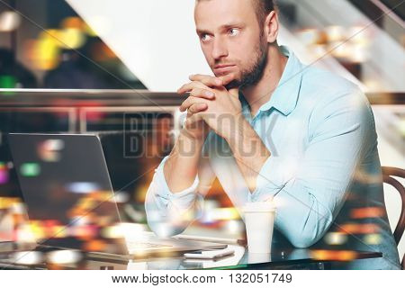 Young businessman having lunch and working in a cafe on blurred background