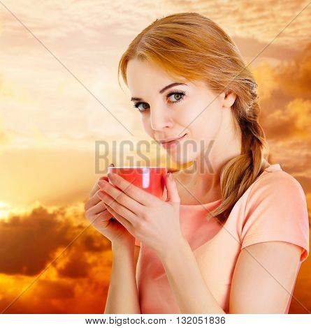 Beautiful girl enjoying a cup of tea on cloudy sunset background