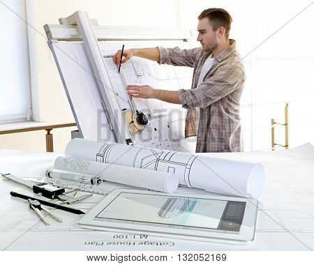 Table with construction drawings and male architect working on blueprints