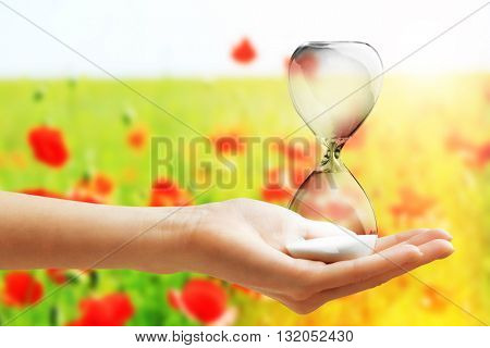 Hourglass in female hand on field of poppies background