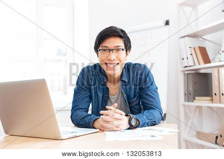 Portrait of cheerful asian young businessman working with laptop on workplace