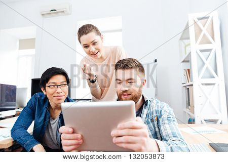 Three concentrated young businesspeople working with tablet together