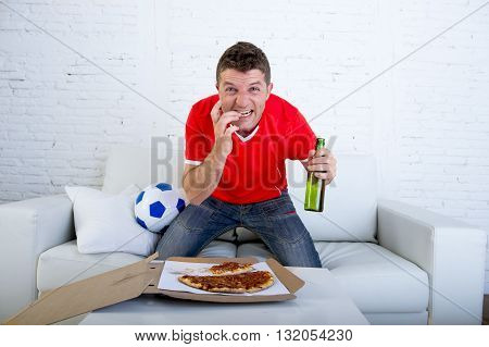 young man alone holding beer bottle eating pizza in stress wearing team jersey watching football game on television at home living room sofa couch excited in disbelief face expression