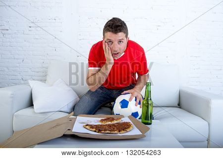 young man alone holding ball with beer and pizza in stress wearing team jersey watching football game on television at home living room sofa couch excited in disbelief face expression