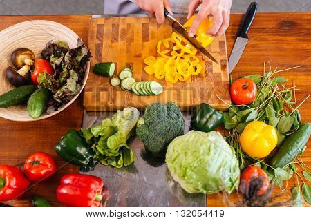Top view of hands of chef cook cutting vegetables and making salad on wooden table