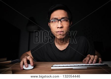 Concentrated asian young man in glasses working with computer in dark room