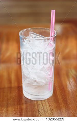 Ice in the glass is placed on the the dining table and have pink suction tube.