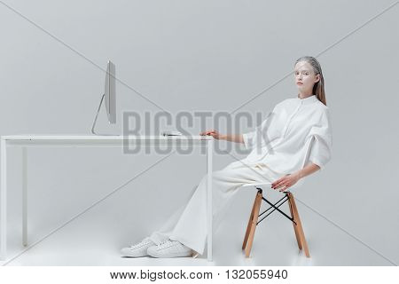 Beautiful fashion woman relaxing at the table with computer on the chair over gray background